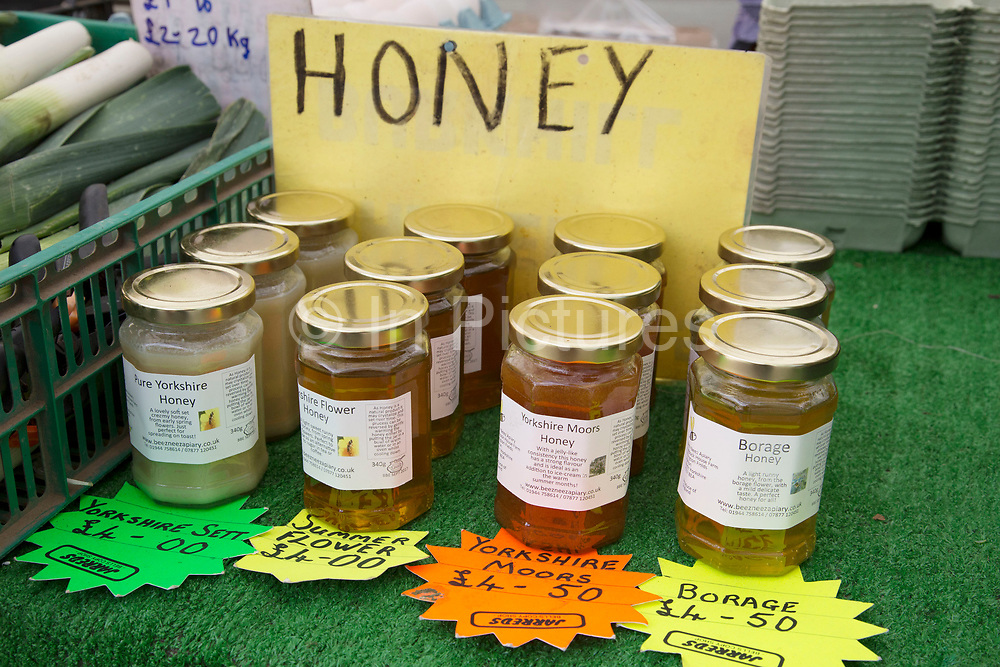 Home produced honey in jars. Local community Sunday market in the village of Husthwaite, North Yorkshire, England, UK. Over 20 stalls with a mixture of old favourites and new stalls lelling locally made products.