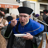 VENICE, ITALY - FEBRUARY 20:  A man wearing and Chinese costume eats  traditional Venetian spaghetti  along the Cannaregio Canal during the Venetian Feast on February 20, 2011 in Venice, Italy. During the Venetian Feast a traditional water parade sails from San Marco along the Canal Grande to the  district of Cannaregio where there the crowd waits for the Svolo della Pantegana  (flight of the mouse).