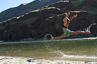 Young woman jumping in water. Rafting Hell's Canyon of the Snake River, ID / OR. Hell's Canyon is the deepest canyon in North America.