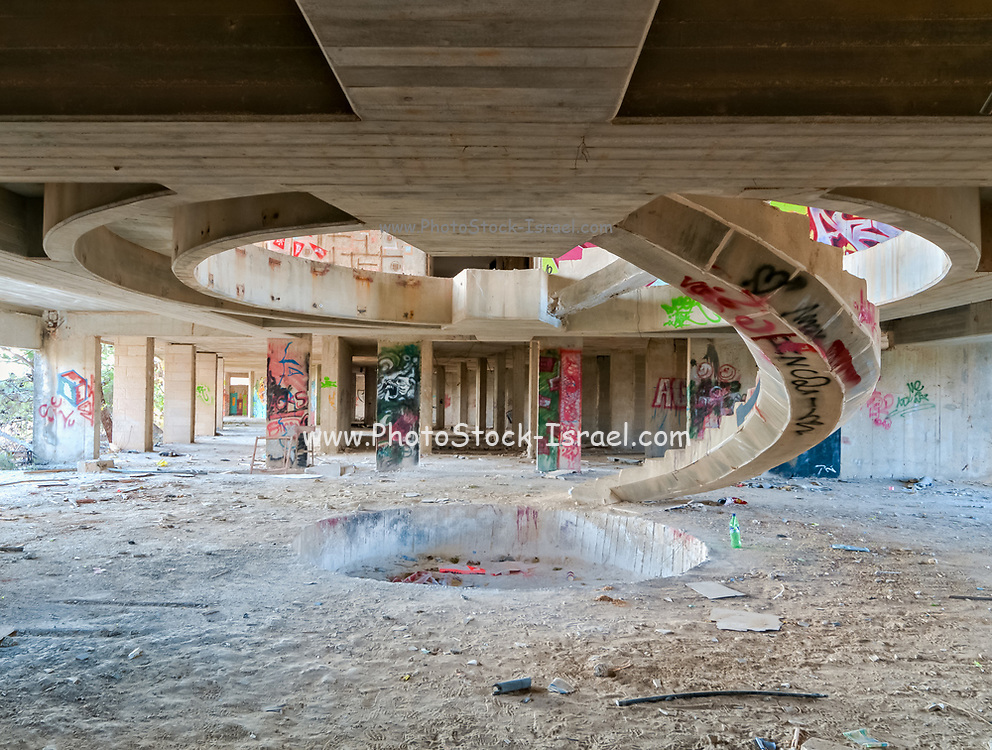 A concrete spiral stairway in an unfinished, abandoned building