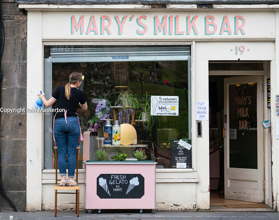 Edinburgh, Scotland, UK. 12 July, 2020, Business slowly returning to normal in Edinburgh city centre. Tourists still almost non existent and streets remain very quiet in the Old Town. Woman cleans windows of Mary's Milk Bar cafe in The Grassmarket. Iain Masterton/Alamy Live News