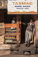 Men pose at their wine shop in India.