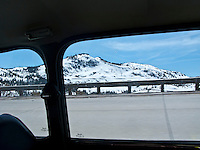 view out the windows while climbing to Donner Pass in a classic Mini Cooper automobile with snow on the mountain slopes and railroad snow sheds,