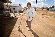 """24 JANUARY 2010 -- WENDEN, AZ:  Jose Montes, (CQ) a 14 year resident of Wenden, takes a break while cleaning the front of his home. During the break he said, """"This is a lot of work for one person."""" Wenden was slammed by its second 100 year flood in 10 years on Thursday night when water raced through Centennial Wash and into the small town in La Paz County west of Phoenix. Most of the town's residents were evacuated to Red Cross shelters in Salome, about 5 miles west of Wenden.     PHOTO BY JACK KURTZ"""