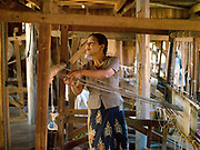 A woman threads her loom at a weaving workshop in Inpawkhone, a village of stilt houses on Inle Lake, Shan State, Myanmar (Burma). The fabric will be woven out of a combination of lotus plant fibres and silk.