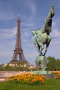 The Eiffel Tower in Paris with a statue of a horse seen from behind in the foreground in a park on the island allee allée des cygnes Pont bir hakeim on the Seine river with flowers
