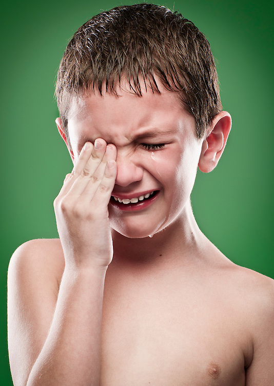 Portrait of boy crying, hands on face.