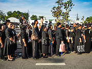 22 NOVEMBER 2016 - BANGKOK, THAILAND:  People dressed in black mourning clothes wait to enter Sanam Luang in Bangkok. Hundreds of thousands of Thais gathered across Thailand Tuesday to swear allegiance to the Chakri Dynasty, in a ceremony called Ruam Phalang Haeng Kwam Phakdi (the United Force of Allegiance). At Sanam Luang, the Royal Parade Ground, and location of most of the mourning ceremonies for the late King, people paused to honor His Majesty by singing the Thai national anthem and the royal anthem.      PHOTO BY JACK KURTZ