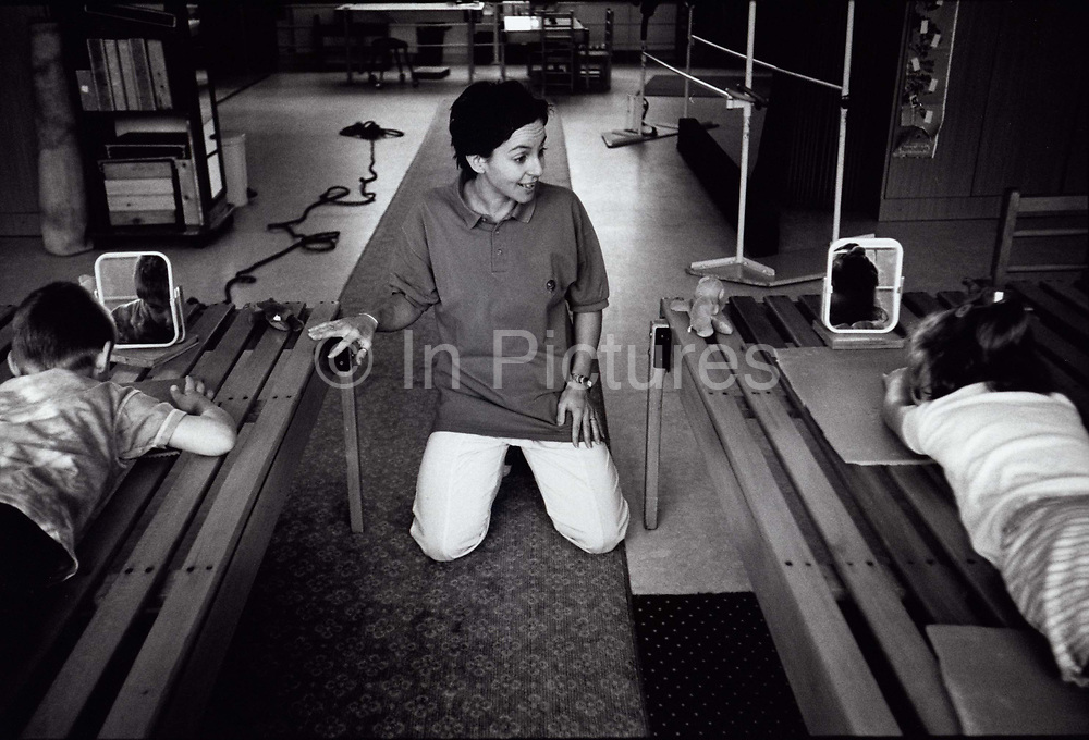 Illy, a Conductor gives instructions to her two young charges during a therapy session at the  Peto Institute, Budapest
