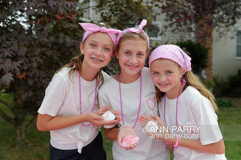 Merrick, New York, U.S. August 15, 2020. Tweens, L-R, ISABELLE, MADDY, and ANNIE FITZPATRICK, hold three of many shells they and friends painted, to raise funds to donate to American Cancer Society Making Strides Against Breast Cancer. The trio formed Lizzie's Army after Annie's 24-year-old sister Lizzie Fitzpatrick was diagnosed with Triple Negative Breast Cancer in late June. Over $3,000 has been raised so far through shell sales and GoFundMe.