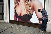People interact with an oversized advertising poster for underwear at H&M on Oxford Street in London, United Kingdom. The advert depicts a young woman wearing a bra.