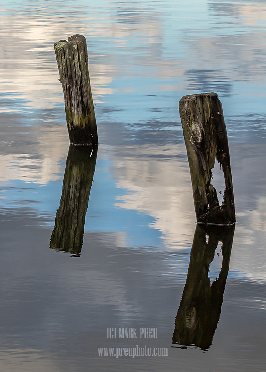 Two posts and their reflections in the West Reservoir in the Bell's Neck Conservation Area
