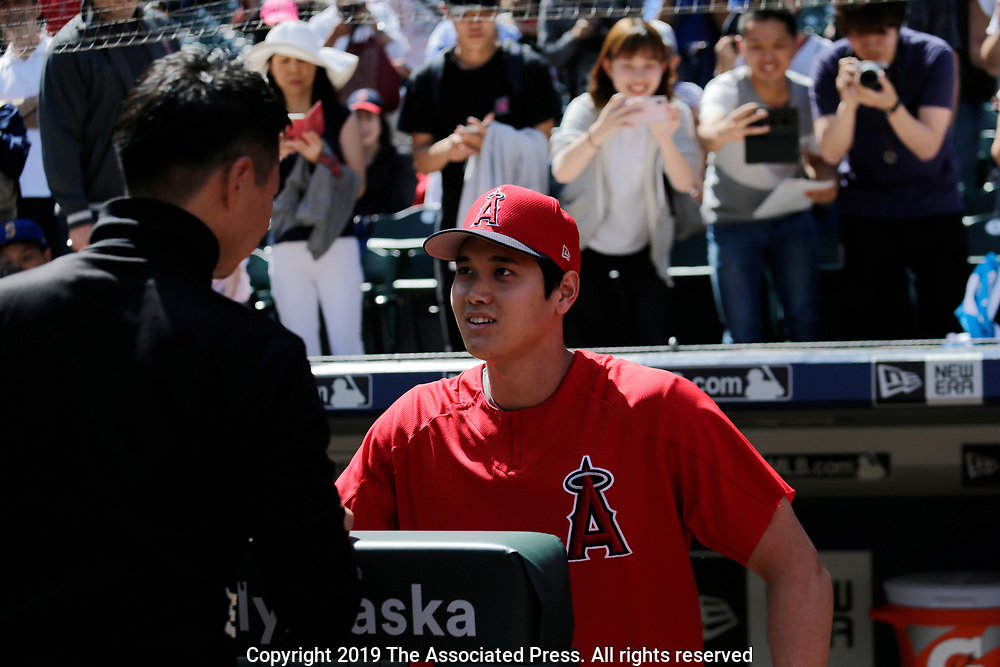 Los Angeles Angels' Shohei Ohtani greets on field fans with others taking photographs behind during batting practice before a baseball game against the Seattle Mariners, Saturday, June 1, 2019, in Seattle. (AP Photo/John Froschauer)