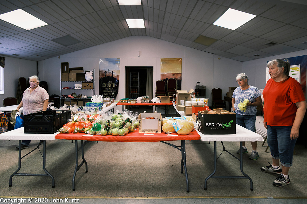 """16 SEPTEMBER 2020 - MITCHELLVILLE, IOWA: Volunteers set up the food pantry at Heritage Word of Life Church. There is no grocery store in Mitchellville, a small community in eastern Polk County. It doesn't qualify as a """"food desert"""" under USDA guidelines because there are grocery stores within 10 miles in neighboring communities, but based on state data, Mitchellville is the poorest community in Polk County (which includes the Des Moines metropolitan area). The Mitchellville zip code has the lowest per capita income in Polk County. Many people don't own cars and can't get to neighboring communities to buy groceries. The library in Mitchellville has made arrangements with a neighboring community to serve hot meals. Every day someone from the Mitchellville library picks up hot meals from a nearby town and distributes them in the library. Heritage Word of Life, a church across the street from Library, has a food pantry in their Fellowship Room where people can pick up fresh vegetables, staples, and hygiene needs.      PHOTO BY JACK KURTZ"""