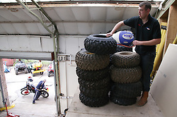 Man with Cerebral Palsy working as mechanic; stacking tyres from all terrain vehicles in workshop,