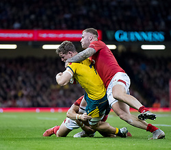 Michael Hooper of Australia is tackled by  Ross Moriarty of Wales<br /> <br /> Photographer Simon King/Replay Images<br /> <br /> Under Armour Series - Wales v Australia - Saturday 10th November 2018 - Principality Stadium - Cardiff<br /> <br /> World Copyright © Replay Images . All rights reserved. info@replayimages.co.uk - http://replayimages.co.uk