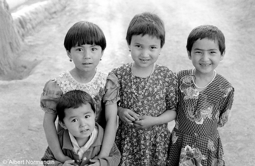 Three girls and young boy in small village