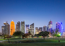 Night view of skyline along Corniche towards modern office towers in West Bay district in Doha Qatar