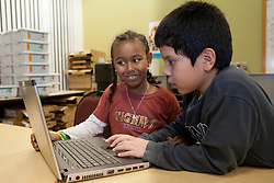 North America, United States, Seattle, after-school technology class, boy and girl using laptop pc