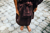 A monk holds prayer beads in his hand while walking the temple grounds.