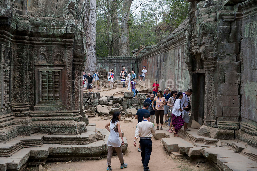 Tourists explore the ancient ruin of the Ta Prohm temple, known as the jungle temple,  in Angkor region Siem Reap Province, Cambodia, South East Asia. UNESCO inscribed Ta Prohm on the World Heritage List in 1992. Today, it is one of the most visited complexes in Cambodia made famous by the Tomb Raider film in 2001.
