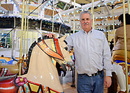 Garden City, New York, USA. March 9, 2019.  GARY MONTI, the Director of Museum and Theater Operations, Cradle of Aviation, poses standing next to horse on Nunley's Carousel, during Unveiling Ceremony of mural of close-up of Nunley's Carousel lead horse. Event was held at historic Nunley's Carousel in its Pavilion on Museum Row on Long Island.