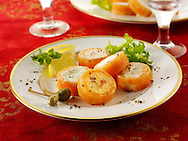 Smoked salmon rolls filled with cream cheese and cream cheese and peppers, in a party buffet setting.