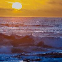 Surf waves break at sunset along California's Pacific Ocean coast near Half Moon Bay.