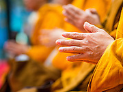 11 JANUARY 2015 - BANGKOK, THAILAND:  A detail photo of a monk's hands during a chanting ceremony to practice the Eight Precepts during a three day retreat at Wat Dhamma Mongkol in Bangkok. Buddhist precepts are moral guidelines Buddhists follow rather than commandments in the Christian sense of the word. As Buddhists develop in the Dhamma, they find that the Precepts grounds their practice. One cannot waver and purposely break any of the Precepts. The Eight Precepts are typically also practiced during intensive meditation retreats of one day or longer. Wat Dhamma Mongkol, (pronounced 'Dhammamongkon') is on the edge of Bangkok, and visible from a number of places, especially from the elevated expressways around the city. The temple was started in the early 1960s by a revered monk who had spent more than 20 years in a forest retreat. The 95 meter high tower, completed in 1985, is a modern rendition of the tower that now marks the place of the Buddha's enlightenment in Bodhgaya, India. There are classrooms, a museum and meditation area inside the tower. The largest Buddha statue carved from a single piece of jade is on the temple grounds.   PHOTO BY JACK KURTZ