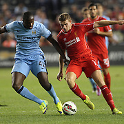 Yaya Touré, (left), Manchester City, challenges Jordan Henderson, Liverpool, during the Manchester City Vs Liverpool FC Guinness International Champions Cup match at Yankee Stadium, The Bronx, New York, USA. 30th July 2014. Photo Tim Clayton