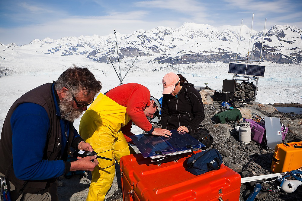 Tad Pfeffer (University of Colorado) checks the aviation radio, in communication with the support helicopter, while Ian Howat and graduate student Julie Markus (Ohio State University) prepare roving GPS units to be deployed on the glacier surface to record the dynamic motion of the Columbia Glacier, Alaska.