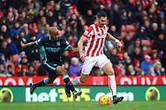 Geoff Cameron of Stoke City (r) is chased by Fabian Delph of Manchester City. Barclays Premier league match, Stoke city v Manchester city at the Britannia Stadium in Stoke on Trent, Staffs on Saturday 5th December 2015.<br /> pic by Chris Stading, Andrew Orchard sports photography.