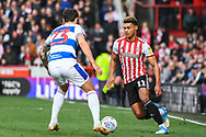Brentford Forward Oliver Watkins (11) and Queens Park Rangers Midfielder Pawel Wszolek (23) in action during the EFL Sky Bet Championship match between Brentford and Queens Park Rangers at Griffin Park, London, England on 2 March 2019.