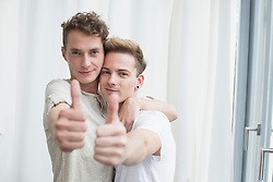 Portrait of homosexual couple showing thumbs up, smiling