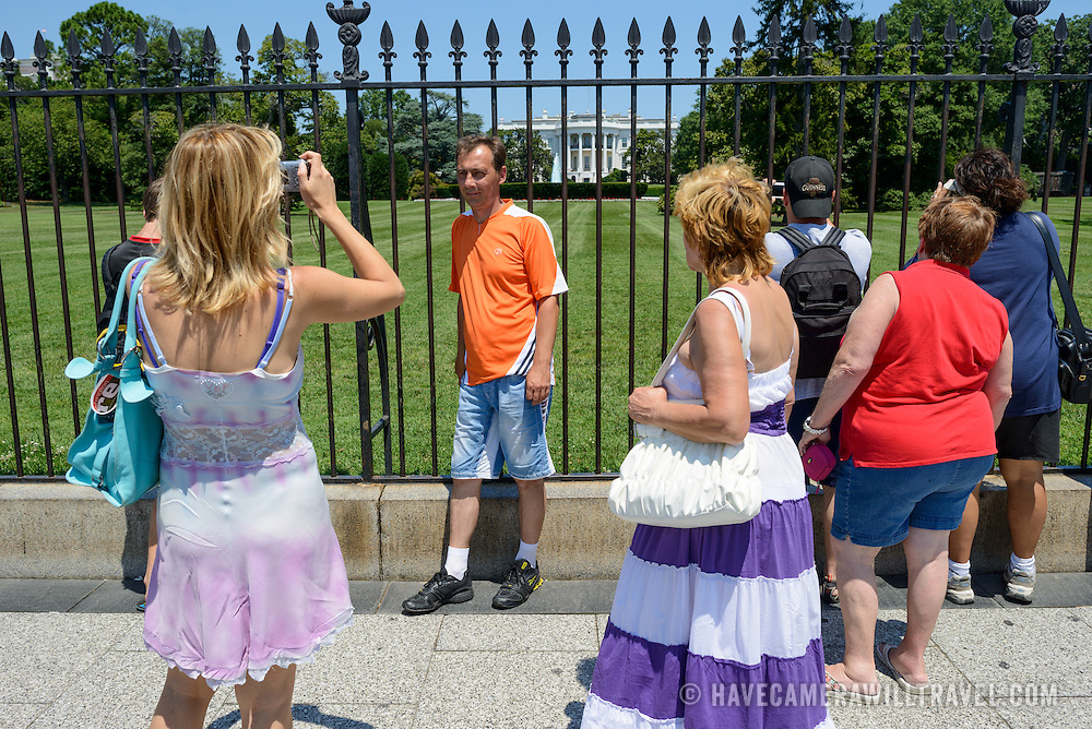 White House Tourists Posing for Photos. Tourists pose for photos in front of the southern side of the White House in Washington DC.