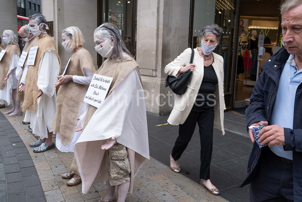 Supporters of environmental and Climate Change group Extinction Rebellion, protest aginst the ethics of the fashion industry outside H&M at Oxford Circus, on 9th September 2020, in London. XR say that the fashion industry produces around 10% of all humanity's carbon emissions, more than all international flights and maritime shipping combined and that over 800,000 tonnes of discarded textile waste annually in the UK.