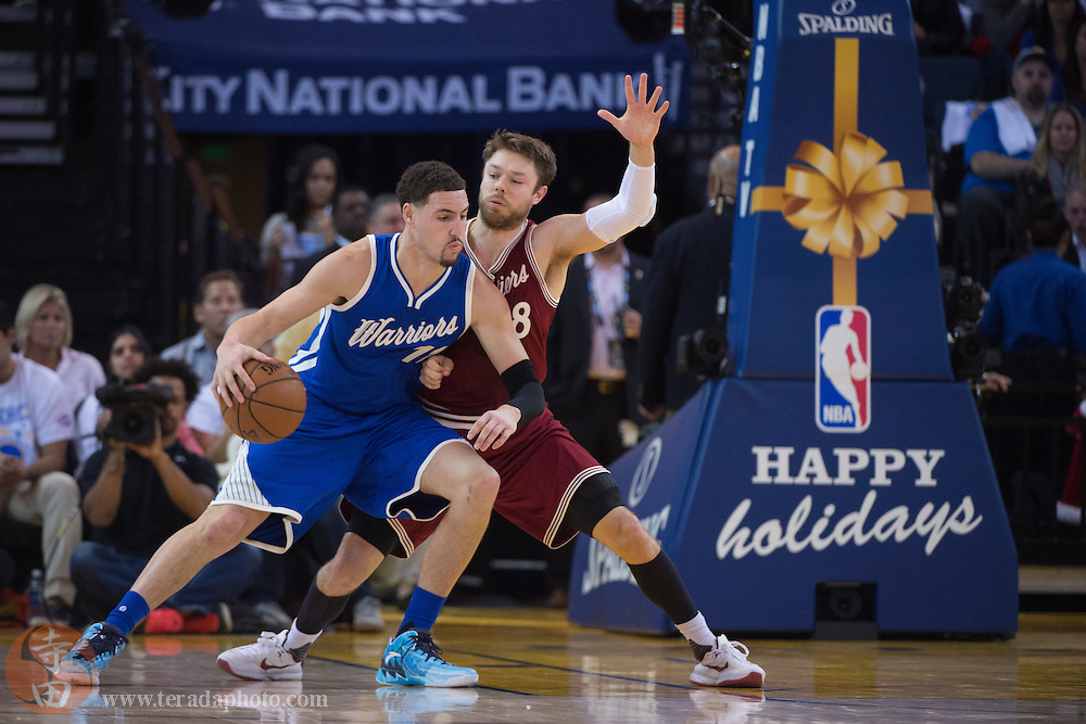 December 25, 2015; Oakland, CA, USA; Golden State Warriors guard Klay Thompson (11) controls the basketball against Cleveland Cavaliers guard Matthew Dellavedova (8) during the second quarter in a NBA basketball game on Christmas at Oracle Arena. The Warriors defeated the Cavaliers 89-83.