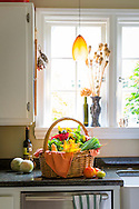 a basket of fresh vegetables and flowers on a countertop in a kitchen