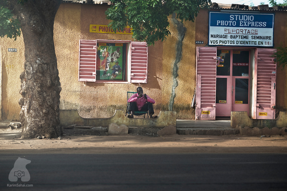 A photographer sitting outside his roadside studio near Ségou, Mali.