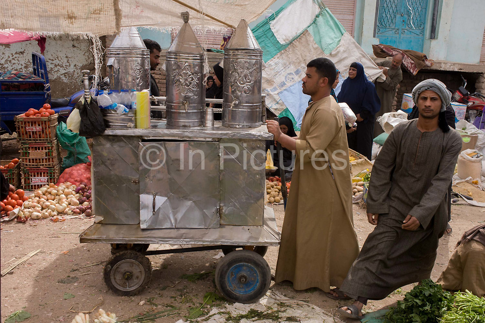 A chai (tea) seller walks through the weekly market at Qurna, a village on the West Bank of Luxor, Nile Valley, Egypt. As he pushes his cart full of hot and cold drinks over the rough dirt path, another local man edges through a gap in this busy market. Amidst the bustle of this busy regular event, people from many miles around have come to trade and buy their provisions.