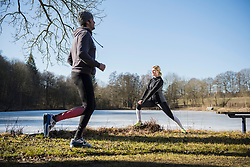 Man jogging while woman stretching on fitness trail in front of frozen lake