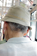 back of elderly man wearing a hat