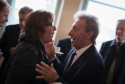 """© Licensed to London News Pictures . 14/10/2013 . Gorton Monastery , Manchester , UK . Footballer Denis Law (right) talks to Hazel Gibb (cousin of Robin and Barry Gibb) (left) . The Humanist funeral of photographer Harry Goodwin , attended by footballers and other celibrities and featuring music by artists he had photographed including """"He Ain't Heavy, He's My Brother"""" by the Hollies and """" Happiness """" by Ken Dodd . Photo credit : Joel Goodman/LNP"""