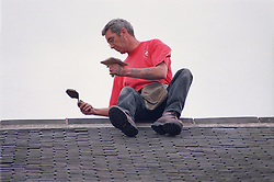 Builder sitting on roof using mortar to repoint ridge tiles,