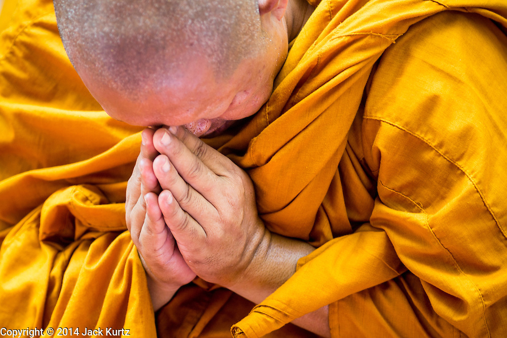 09 OCTOBER 2014 - BANGKOK, THAILAND: A Buddhist monk prays for Bhumibol Adulyadej, the King of Thailand in the plaza in front of SIriraj Hospital. The King has been hospitalized at Siriraj Hospital since Oct. 4 and underwent emergency gall bladder removal surgery Oct. 5. The King is also known as Rama IX, because he is the ninth monarch of the Chakri Dynasty. He has reigned since June 9, 1946 and is the world's longest-serving current head of state and the longest-reigning monarch in Thai history, serving for more than 68 years. He is revered by the Thai people and anytime he goes into the hospital thousands of people come to the hospital to sign get well cards.   PHOTO BY JACK KURTZ