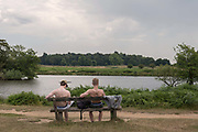 Two topless men sit at a bench in Richmond Park overlooking Pen Ponds as record temperatures soar across England on the 25th July 2019 in Richmond in the United Kingdom. The Met Office has estimated that parts of England could reach a record-breaking 39C this afternoon.
