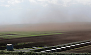 Goshen, New York - Strong winds carry soil into the air over farmers' fields in the Black Dirt region of Orange County on May 8, 2010. ©Tom Bushey / The Image Works