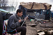 France, Calais, 23 Februari 2015, An Eritrean refugee is cutting his beard in front of his camp.