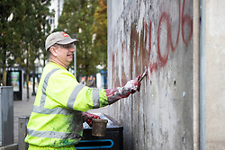 © Licensed to London News Pictures. 16/10/2020. Manchester, UK. A council worker removes some graffiti in Manchester Piccadilly Gardens that says 'THE NORTH IS NOT A PETRI DISH'.  Photo credit: Kerry Elsworth/LNP