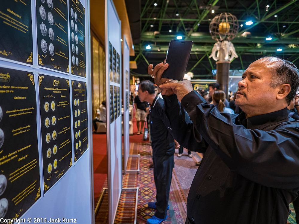 22 DECEMBER 2016 - BANGKOK, THAILAND: A man uses his smart phone to photograph a graphic of commemorative coins honoring the late King at Queen Sirikit Convention Center. The Thai treasury department sold commemorative coins to honor Bhumibol Adulyadej, the Late King of Thailand, at Queen Sirikit Convention Center in Bangkok. Thecoins celebrate milestones in the beloved monarch's life. PHOTO BY JACK KURTZ